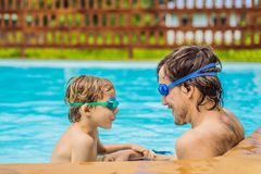 Dad and son in swimming Goggles have fun in the pool royalty free stock image