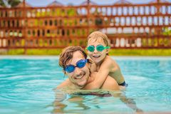 Dad and son in swimming Goggles have fun in the pool royalty free stock photos