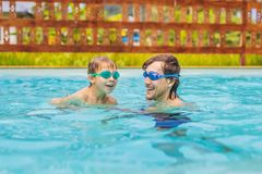 Dad and son in swimming Goggles have fun in the pool royalty free stock images