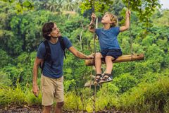 Dad and son on the Swing at the Campuhan Ridge Walk in Ubud, Bali.  royalty free stock photo
