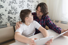 Dad and son   with tablet computer indoor Stock Photo