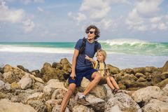 Dad and son travelers on amazing Melasti Beach with turquoise water, Bali Island Indonesia. Traveling with kids concept.  royalty free stock image