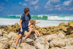 Dad and son travelers on amazing Melasti Beach with turquoise water, Bali Island Indonesia. Traveling with kids concept.  stock photography