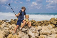 Dad and son travelers on amazing Melasti Beach with turquoise water, Bali Island Indonesia. Traveling with kids concept.  royalty free stock photos