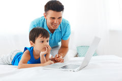 Dad and son using notebook in bedroom Stock Photos
