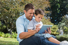 Dad and son using a tablet pc in a park Stock Photos
