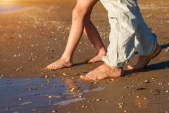 Dad and son walk on the beach barefoot stock images