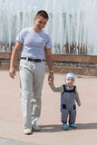 Dad and son walking near the fountain. Stock Image