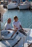 Dad and son on a yacht. Father and son enjoying summer day on a yacht stock photos