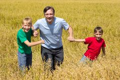 Dad with sons at field Royalty Free Stock Image