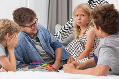 Dad spending time with children. Dad spending time with his three children in living room Royalty Free Stock Images