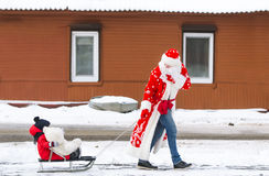 Dad in a suit of Santa Claus and his little son riding the sledge under winter snow, on village street Royalty Free Stock Photo