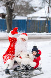 Dad in a suit of Santa Claus and his little son riding the sledge under winter snow, on village street Stock Images