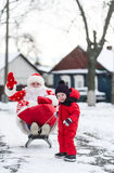 Dad in a suit of Santa Claus and his little son riding the sledge under winter snow, on village street royalty free stock images