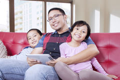 Dad with tablet and children sitting on the couch Stock Photos