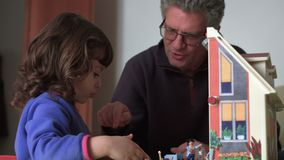 Dad talking with her candid daughter and playing with dollhouse SF. Dad is talking with her candid daughter while are playing with dollhouse stock footage