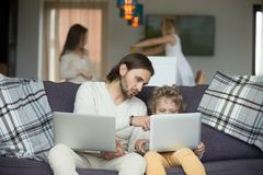 Dad teaching son using laptop sitting on sofa at home. Dad talking to child teaching son using laptop sitting on sofa at home, young father explaining boy how to Royalty Free Stock Photos