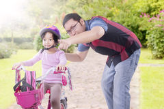 Dad teach daughter to ride bicycle at the park Royalty Free Stock Images