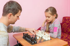 Dad teaches his daughter to make first moves chess Royalty Free Stock Photo