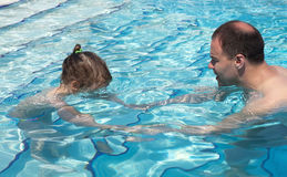Dad teaches his daughter to swim Stock Photos