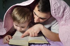 Dad teaches his little son to read a book hiding under the blanket. stock image