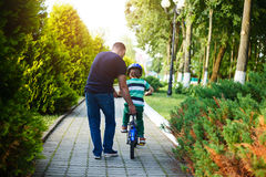 Dad teaches his son riding on bicycle in summer park. Back view.  stock images