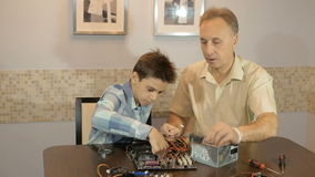 Dad teaches his son a teenager, what`s inside the computer stock video