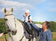 Dad teaches his son to sit in the saddle. royalty free stock photography