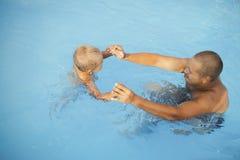 Dad teaches his son to swim Stock Photos