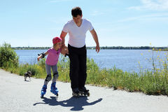 Dad teaches little daughter to roller skate Stock Photos