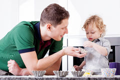 Dad teaches son bake muffins Stock Photography