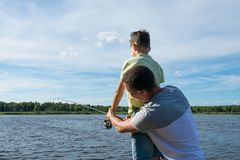 Dad teaches son to fish on spinning on the lake, rear view royalty free stock image