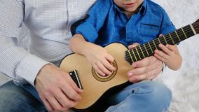 Dad teaches son to play guitar. Hands of dad and son close up. Music, lifestyle, parenting. Slow motion stock video