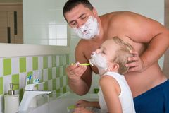 Dad teaches to shave her little son.Child wants to be like dad. Child wants to be like dad.Dad teaches to shave her little son stock photo