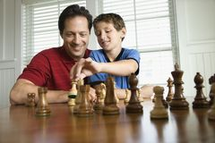 Dad teaching chess to son.