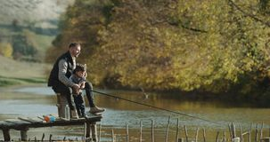 Dad teaching his son how to catch the fish from lake. stock footage