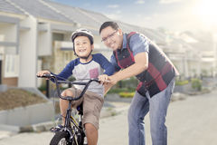 Dad teaching his son to ride a bike. Portrait of happy father teach his son to drive a bicycle on the road, shot outdoors Stock Photo