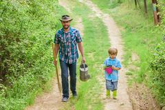 Dad teaching son care plants. Arbor day. Planting trees. Tree planting tradition. Little helper in garden. Planting. Flowers. Growing plants. Boy and father in stock photo