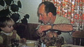 1973: Dad teaching son about how to carve a holiday turkey. stock footage