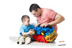 Father teaching son how to repair toy lorry. Learning and early education concept. royalty free stock photo