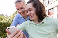 Dad and teen son. Father Day. Young man is showing cell phone screen to parent in park. Concept of family, fatherhood, technology royalty free stock images