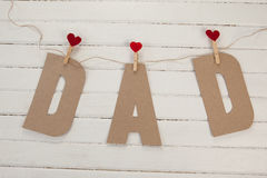 Dad text with cloth pegs hanging on rope. Against wooden background Stock Photo