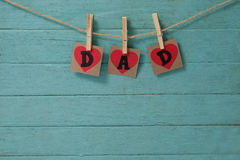 Dad text with cloth pegs hanging on rope. Against wooden background Royalty Free Stock Photography