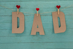 Dad text with cloth pegs hanging on rope. Against wooden background Royalty Free Stock Image