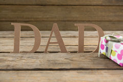 Dad text by gift box on table. Dad text by gift box on wooden table Royalty Free Stock Image