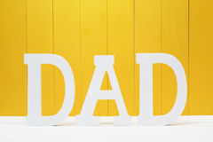 DAD text letters on yellow wooden background Royalty Free Stock Photo
