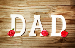 DAD text in white wooden letters with flowers. DAD text in white wooden letters with carnation flowers stock image
