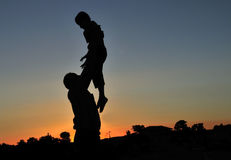 Dad throws the child at sunset Stock Images