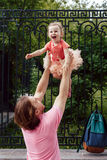 Dad throws daughter happy. Dad in the park playing with her baby by throwing daughter up, Dad and daughter dressed in the pink, Dad and daughter happy family royalty free stock photos