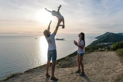 Dad throws his son in the air, and mom looks at them on the mountain with seascape. Dad throws his son in the air, and mom looks at them on the mountain with royalty free stock photo